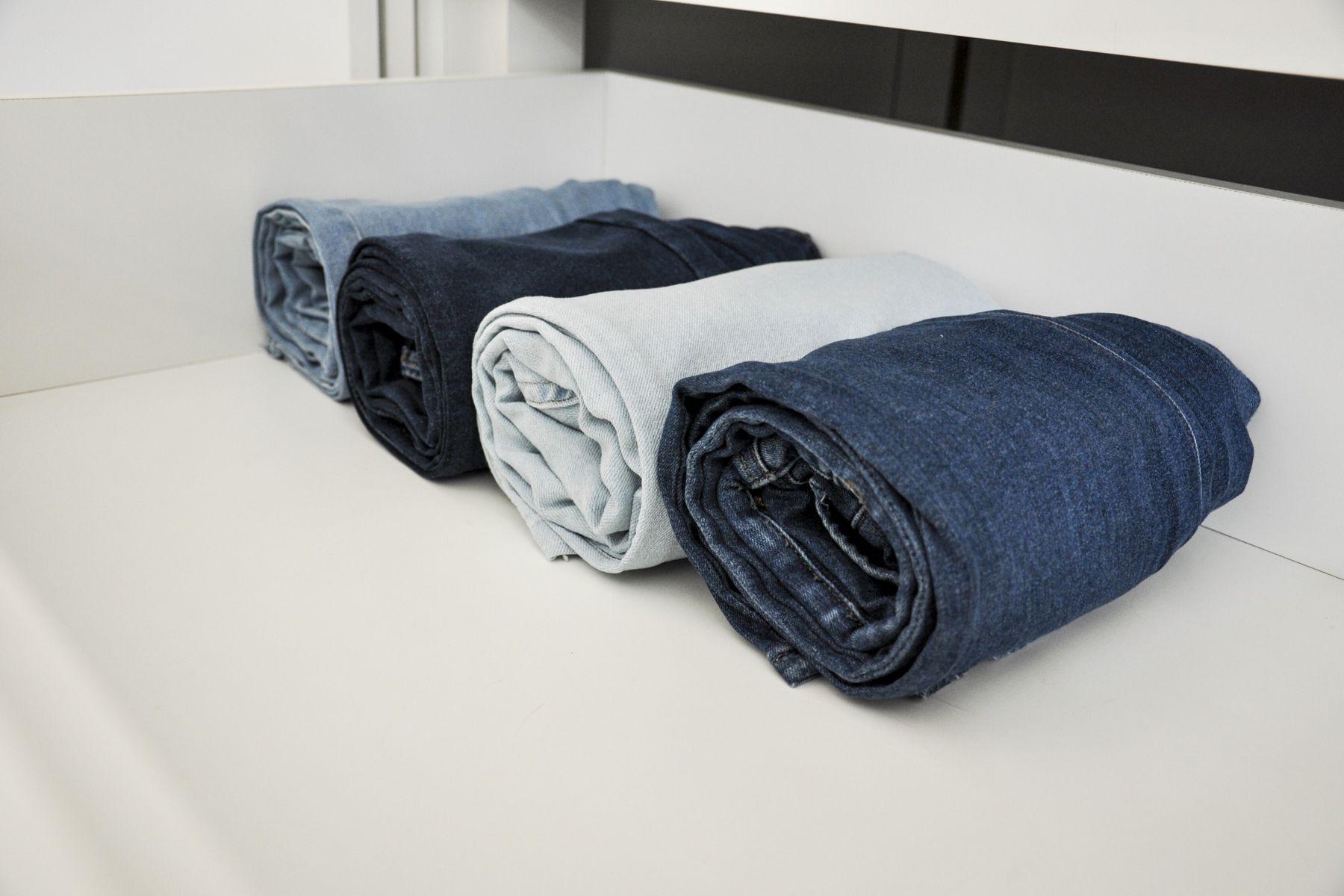 Quatro Calças jeans de tons diferentes dobradas em rolo dentro de uma prateleira no armário