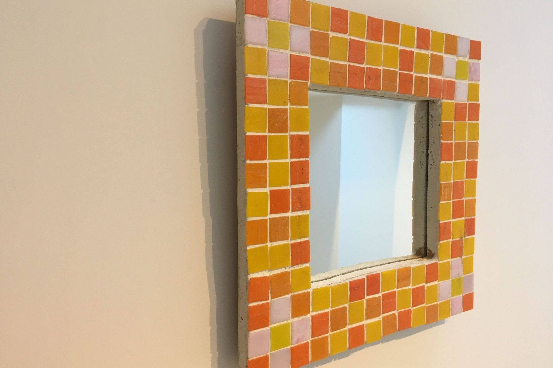 Spiegel mit gelben und orangefarbenen Mosaikrahmen an der Wand hängen