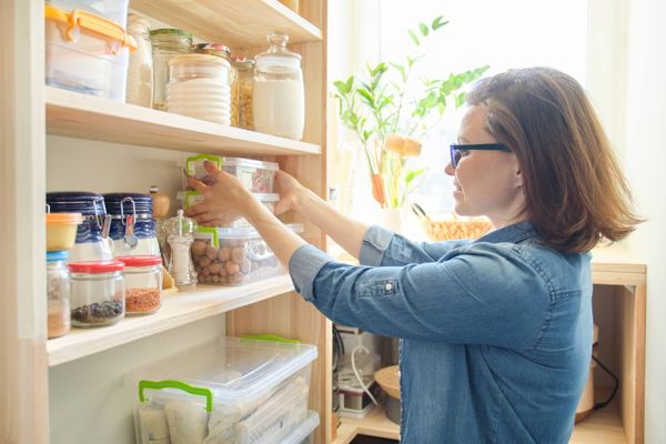 Woman organizing kitchen groceries and supplies