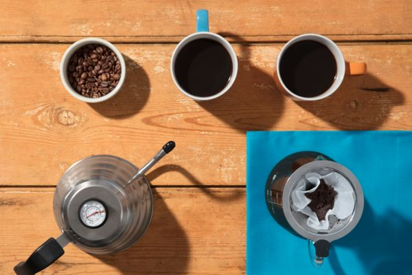 A coffee pot, coffee beans and coffee in mugs on a wooden table