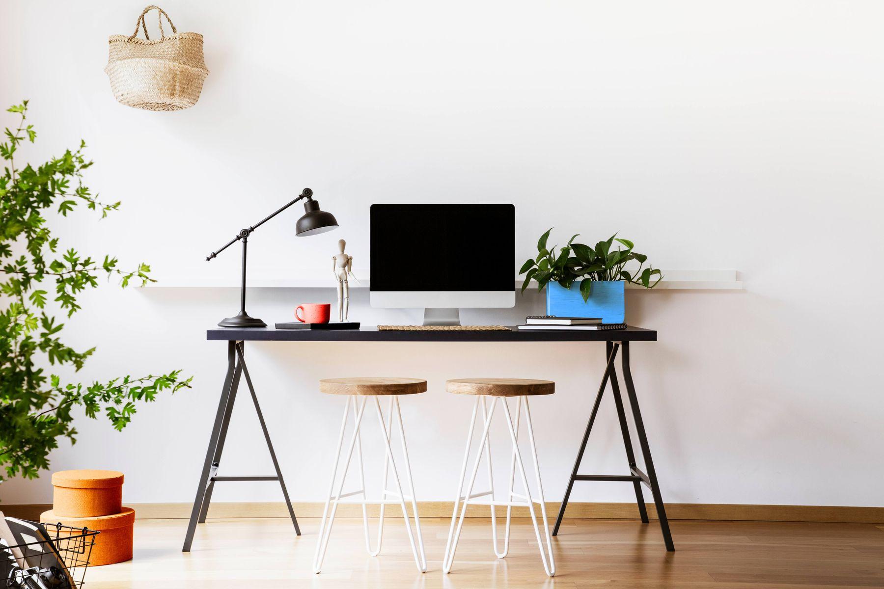 Mesa de trabalho com cavaletes, com luminária e um vaso de planta em cima; e duas banquetas, uma sacola pendurada na parede e uma planta grande no chão
