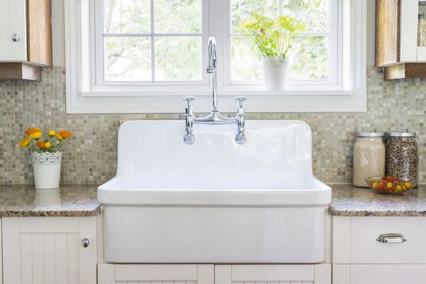 A large white sink sits in the centre with chrome taps brightly lit with a large window behind it and flanked by kitchenware