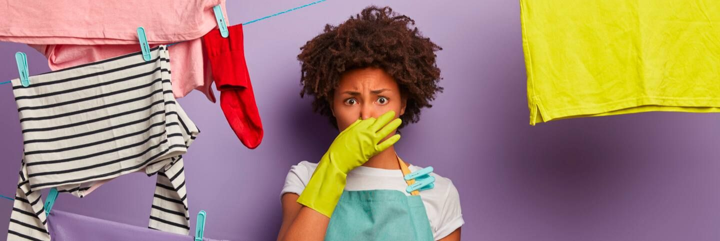 Female wearing yellow house gloves holding nose closed surrounded by laundry