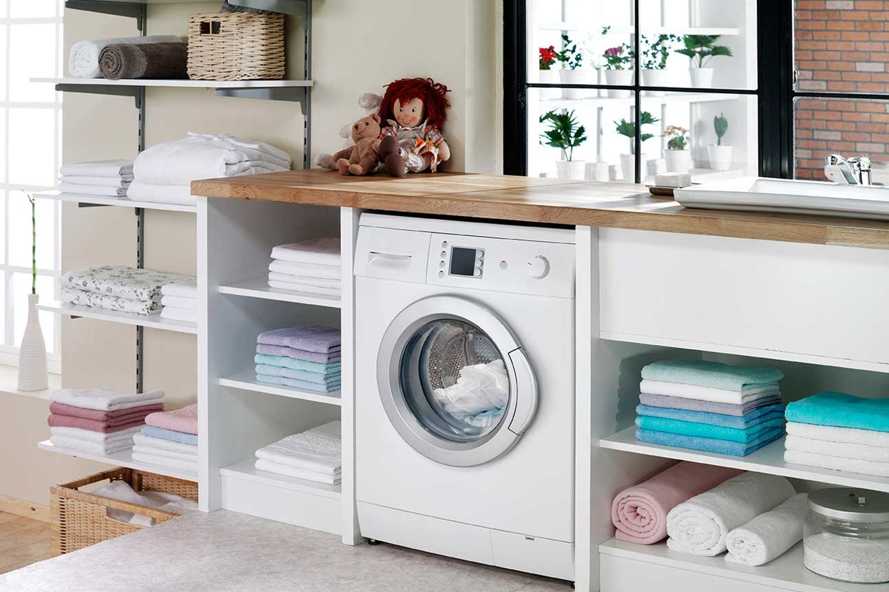 Utility room, featuring a washing machine, shelving and a sink