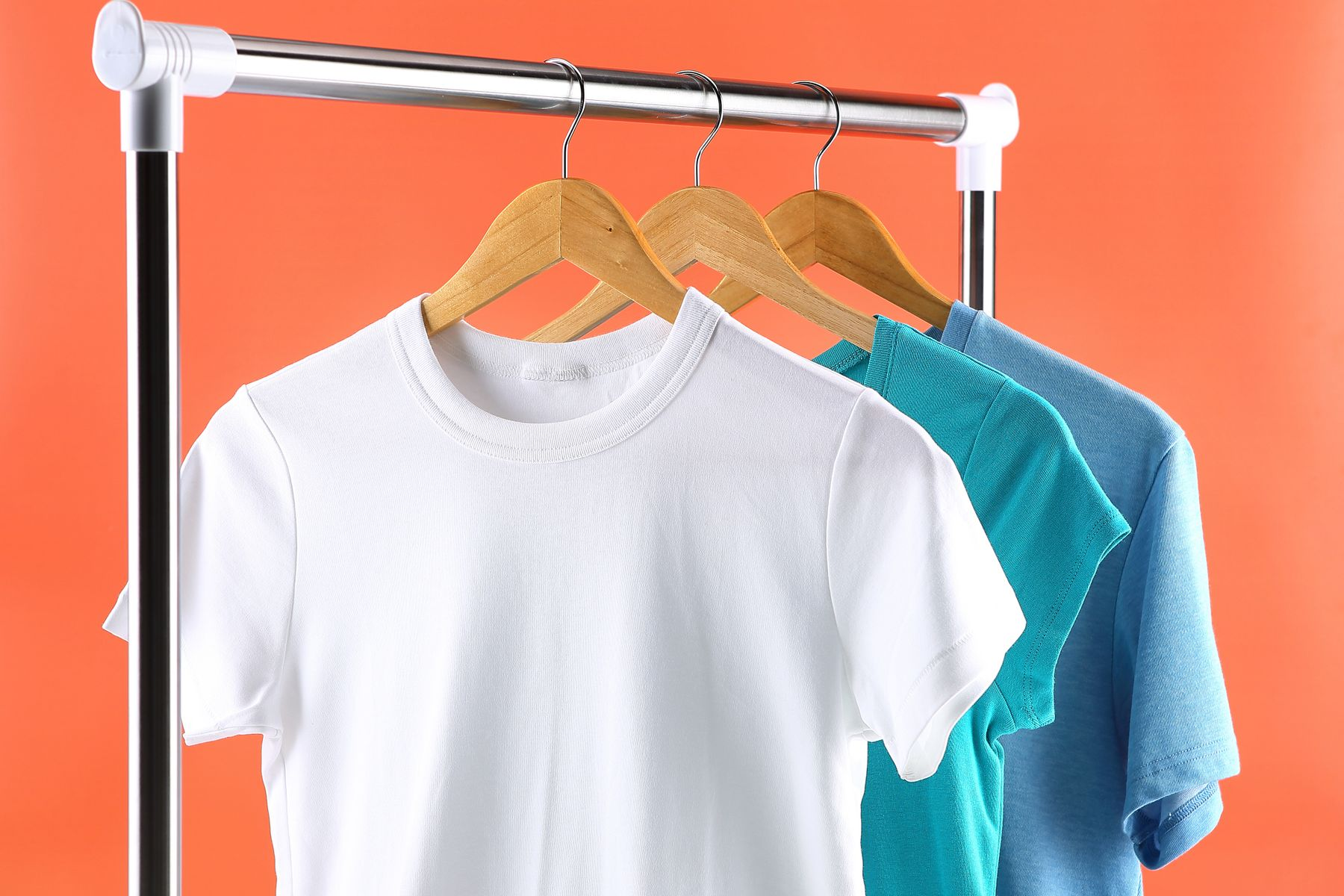 Three cotton t-shirts hanging up on a clothes rail with an orange background