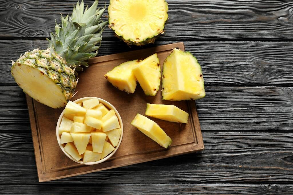 Chopped up pineapple with parts saved for planting a pineapple top