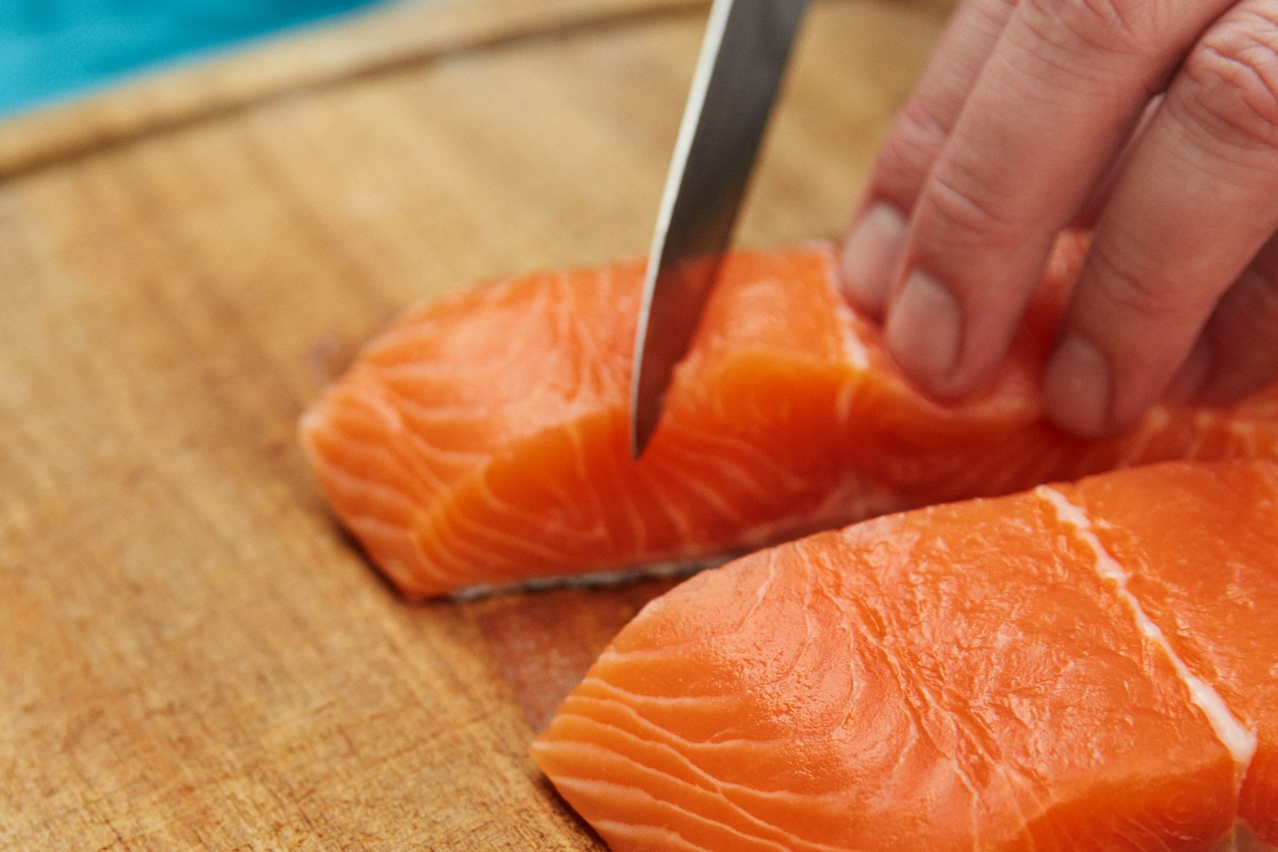 Fillet of salmon being cut with knife on chopping board