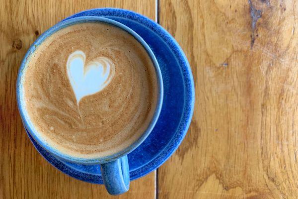 Um coração na espuma de leite da xícara de café azul sobre a mesa