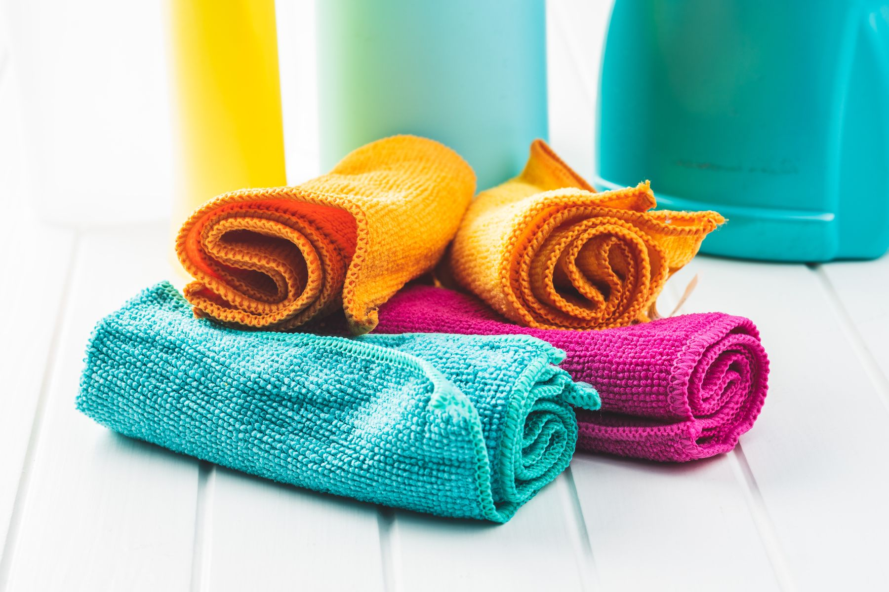 multiple colourful cleaning clothes rolled up on a white surface