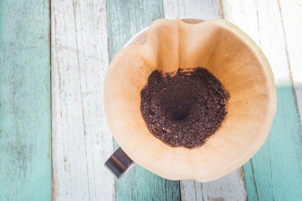 Borra de café no filtro sobre o bule em mesa de madeira pintada