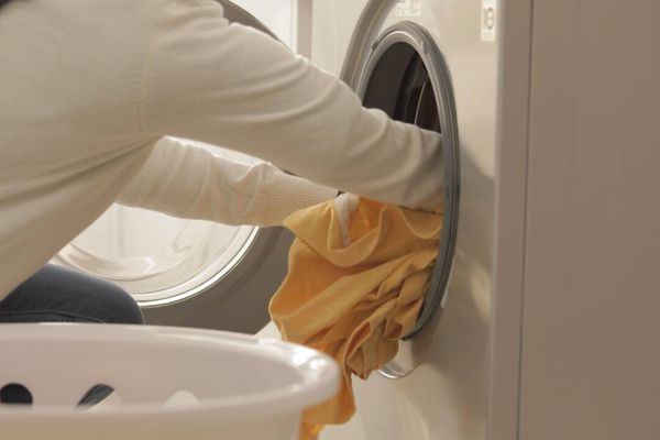 Pessoa colocando roupa para lavar na máquina de lavar roupa com abertura frontal