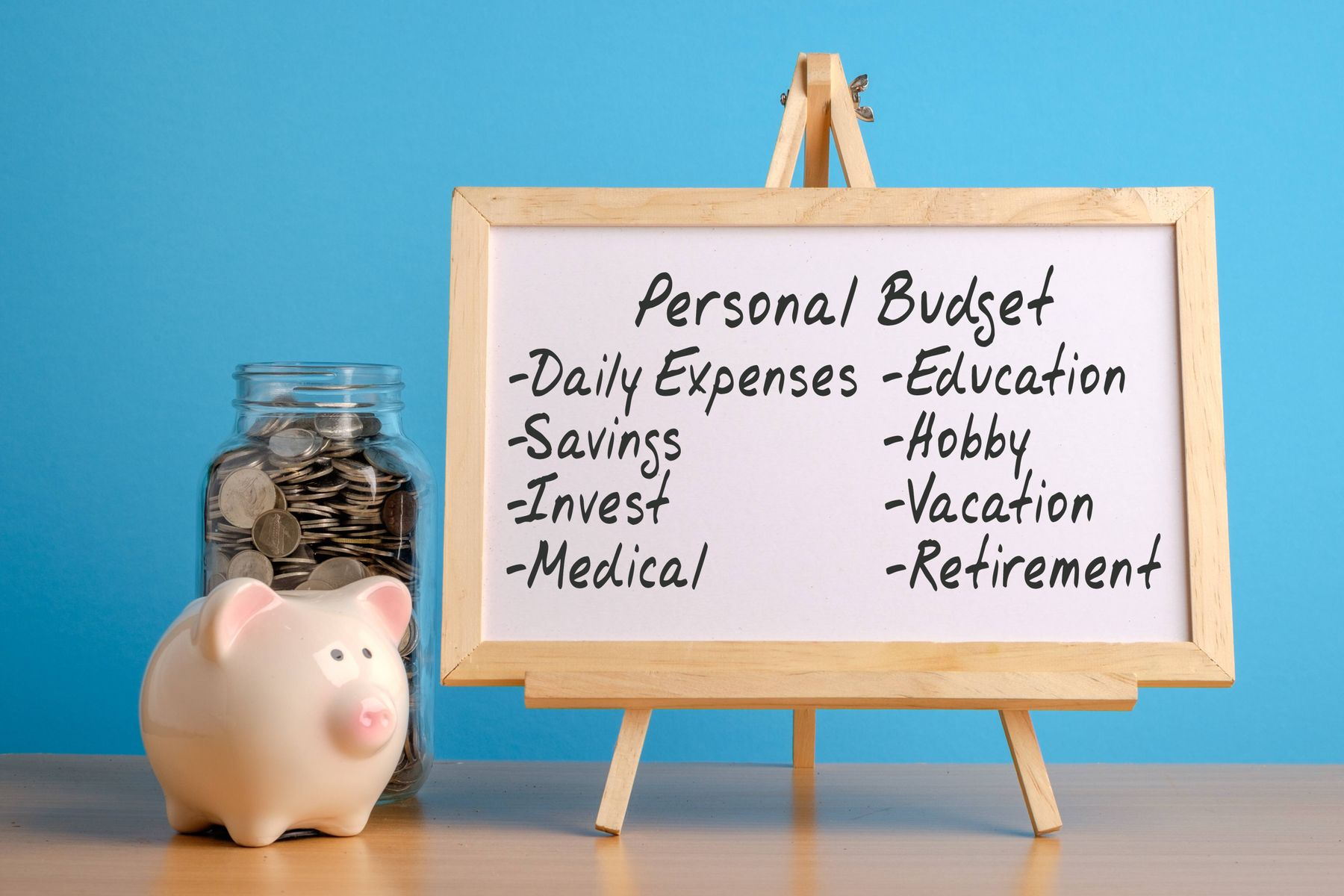 a whiteboard with the personal budget next to a piggy bank and coins
