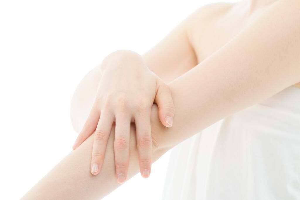woman moisturising arms after shower for sensitive skin treatment