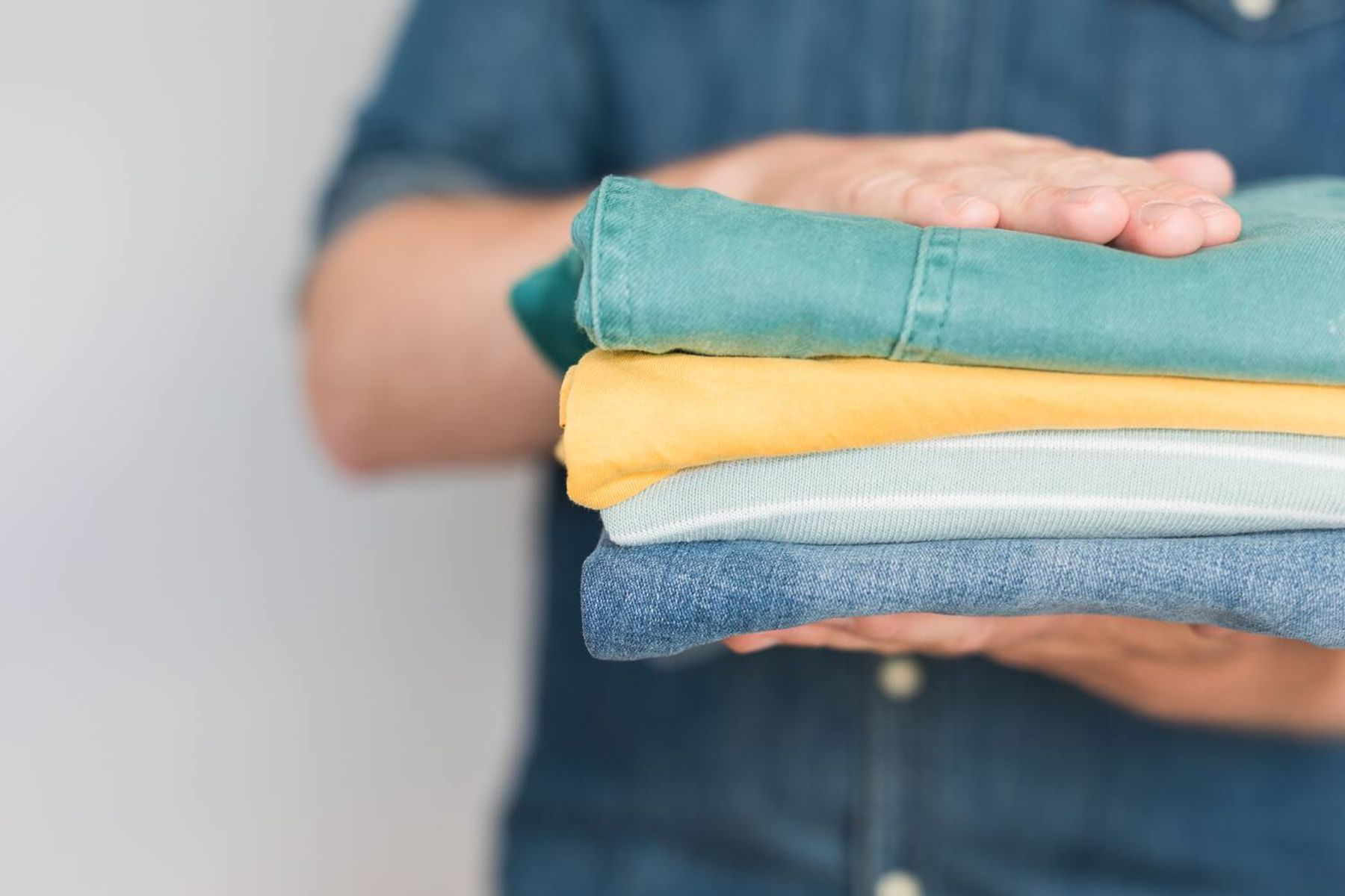 A person holding a stack of folded clothing
