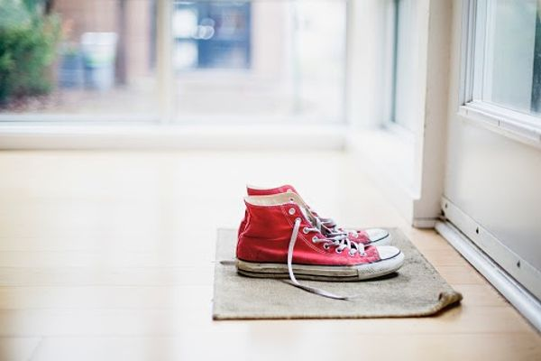 Red sneakers on the entrance door mat
