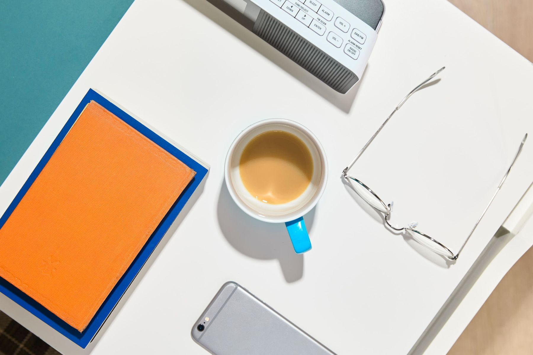 A tidy desk with glasses, a drink, papers and a mobile phone