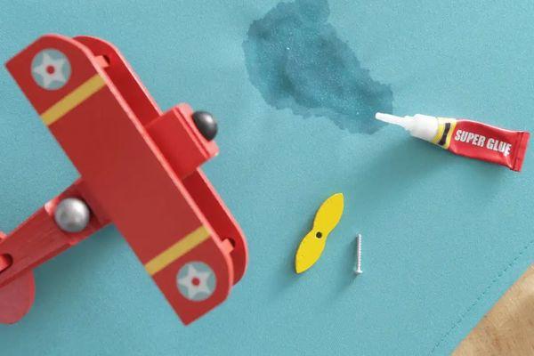 Avión de juguete, tubo de pegamento y mancha de pegamento en tela azul