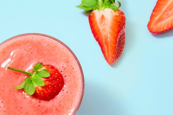remove strawberry stains: pink strawbery smoothie on blue background with slices of fresh strawberry