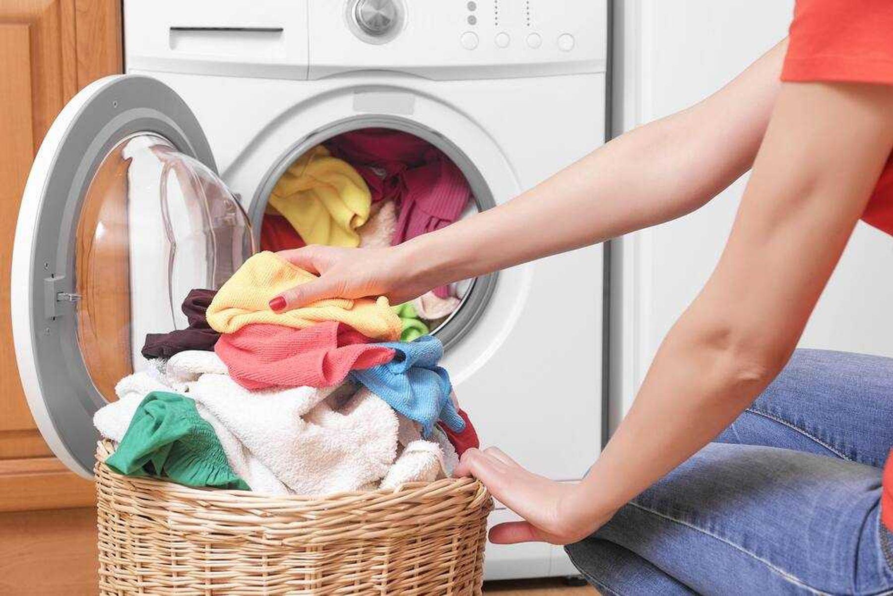 Lấy quần áo ra khỏi máy giặt cửa trước sau khi giặt xong