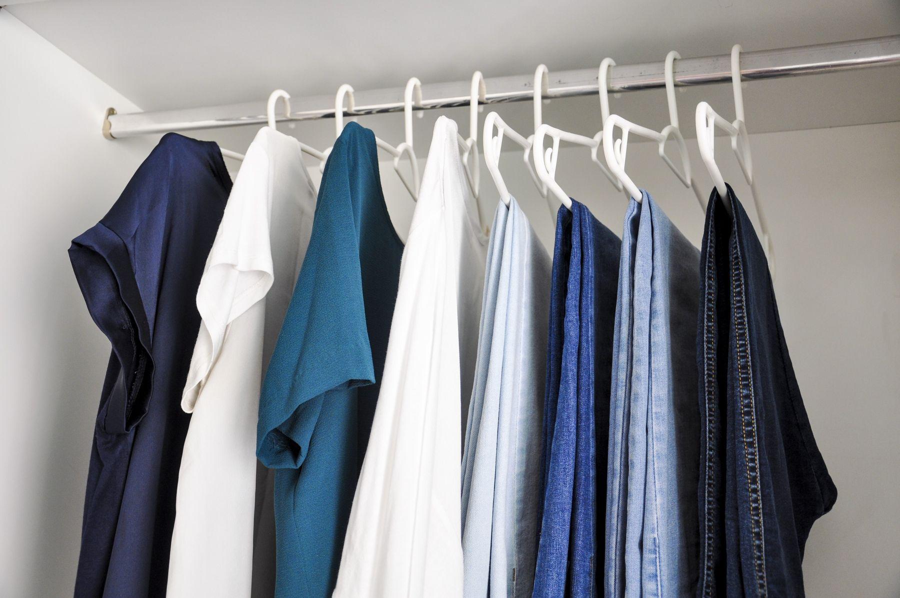 Calças jeans penduradas nos cabides dos armários ao lado de camisetas