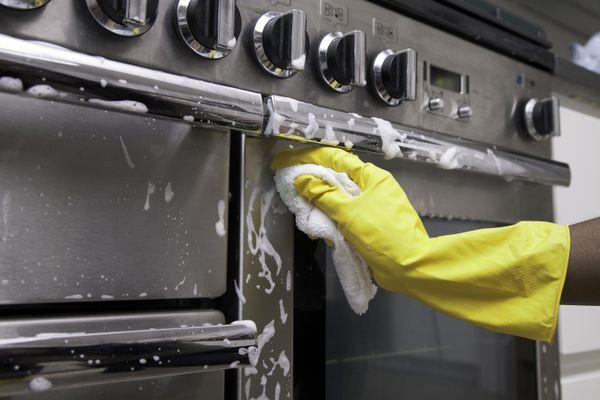 Persona limpiando el horno con guantes de goma