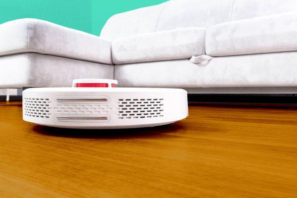 weißes Sofa und Roboter-Staubsauger