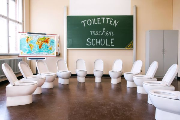 Schultoiletten als Schüler vor Tafel im Halbkreis aufgestellt