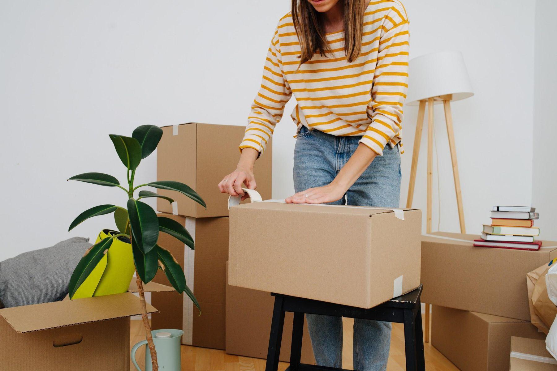Mulher fechando caixa de papelão com fita adesiva