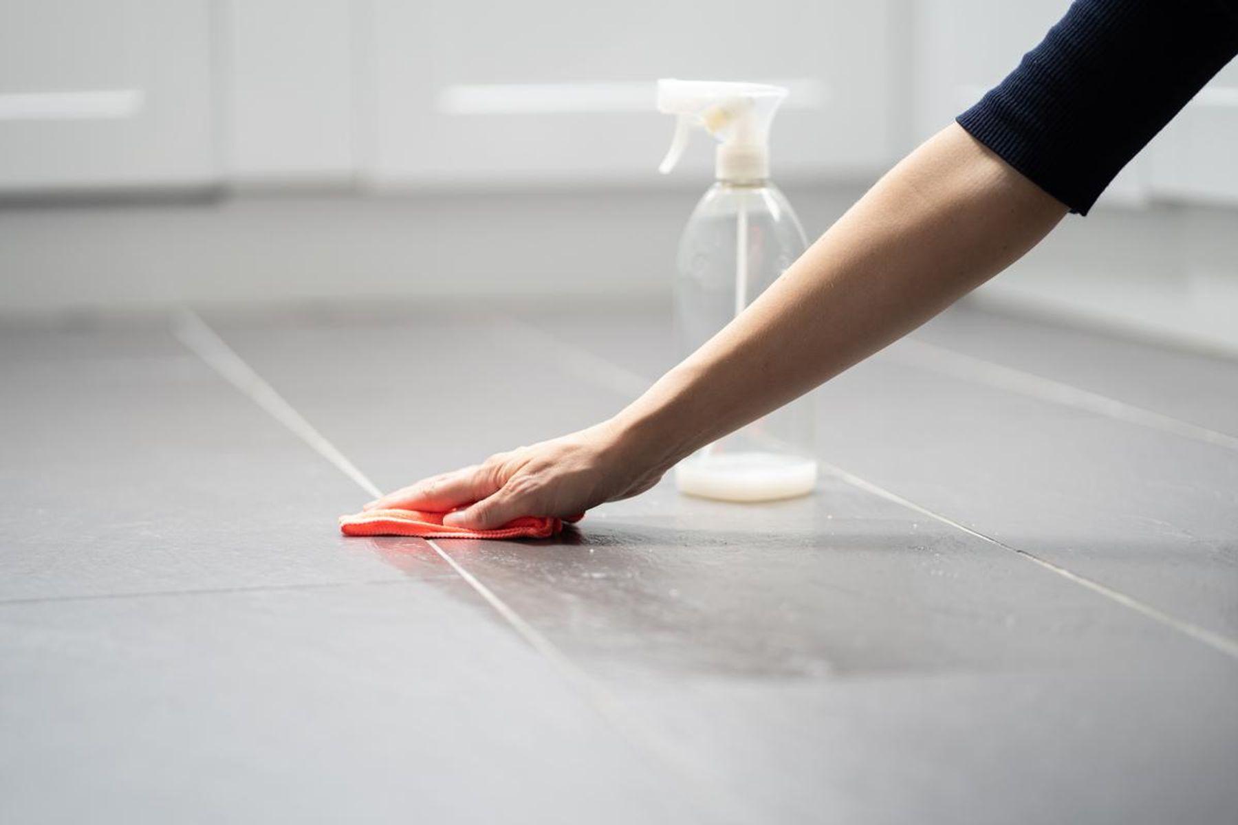 Mão feminina limpando o chão da cozinha com pano e borrifador
