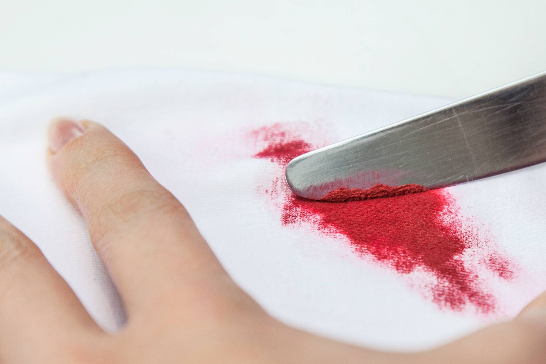 removing a red stain on white fabric with a knife