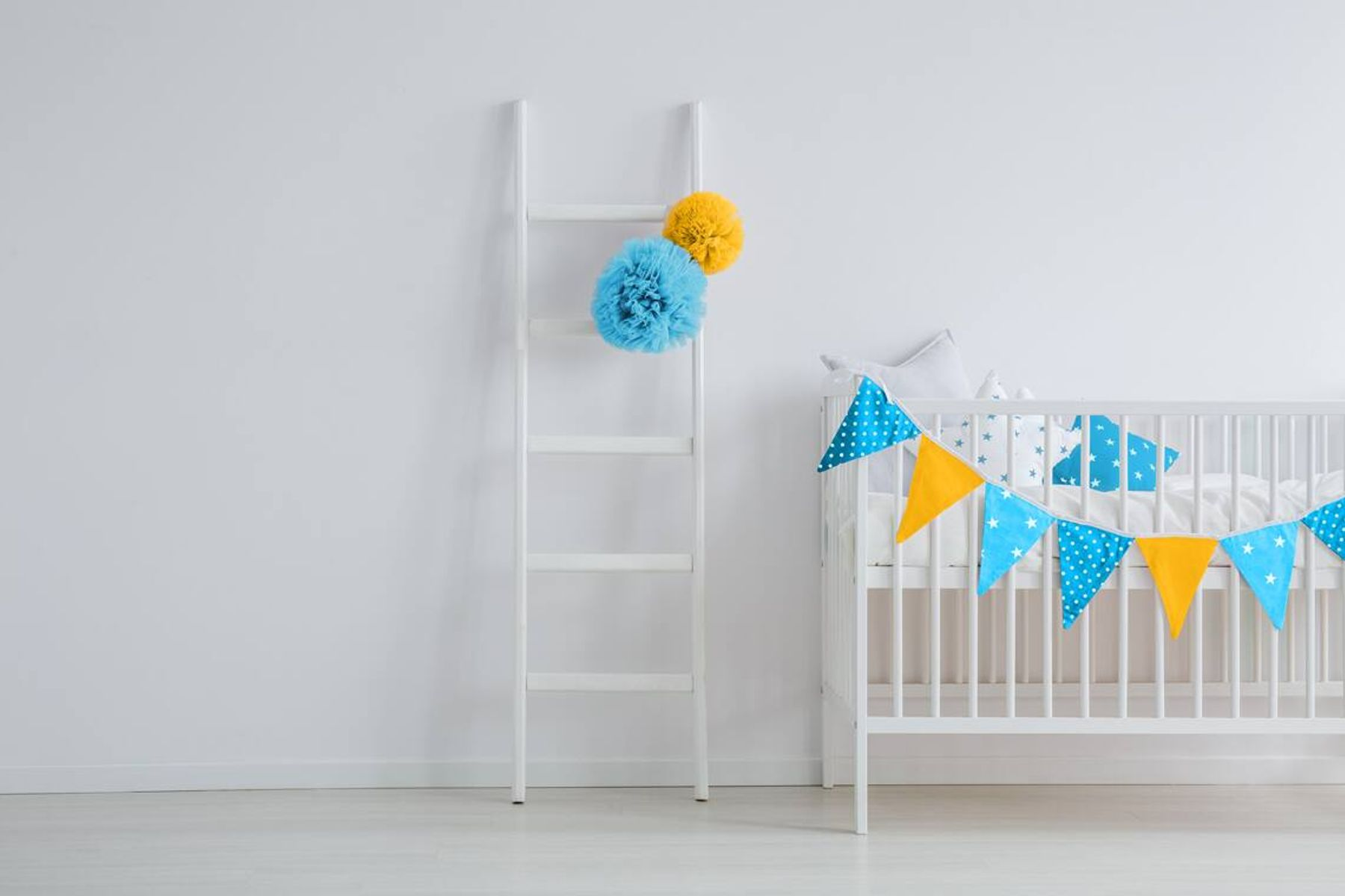 baby proof white cot and colourful bunting against white wall