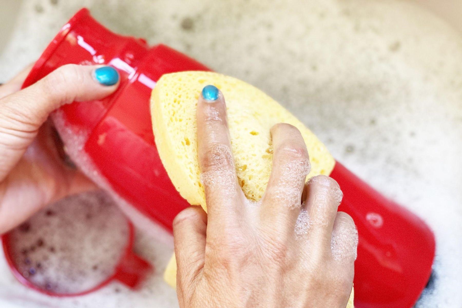 Mãos lavam uma garrafa vermelha na pia com espuma