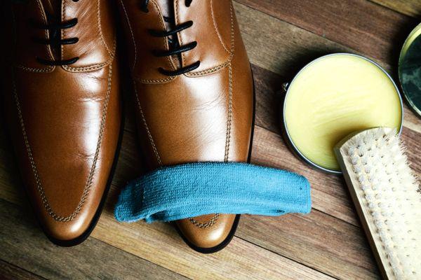 scarpe di pelle marrone con straccio e cera per pulire la pelle