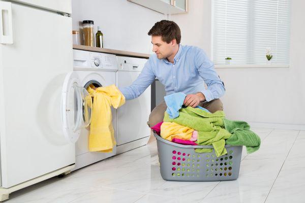 Pessoa colocando roupas na lavadoura para tirar o mau cheiro da roupa