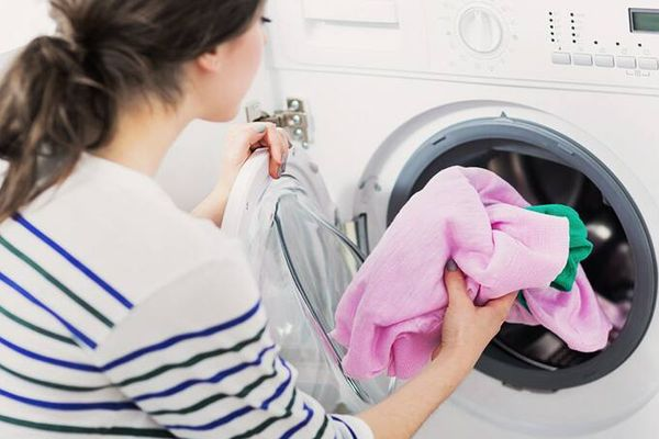 student-putting-clothes-into-washing-machine
