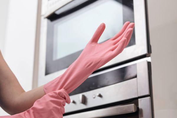 Mão vestida com luva rosa para limpar cooktop