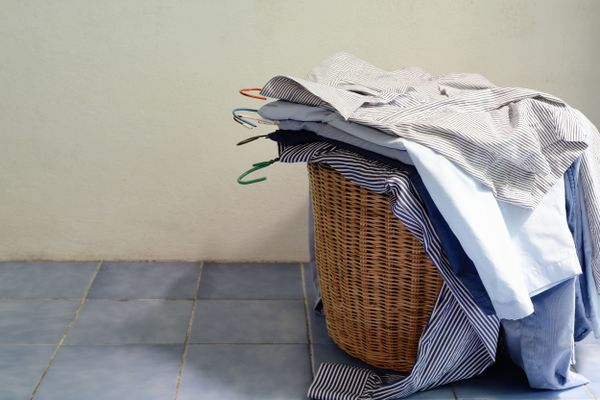 pile of clean ironed shirts on hangers on top of washing basket