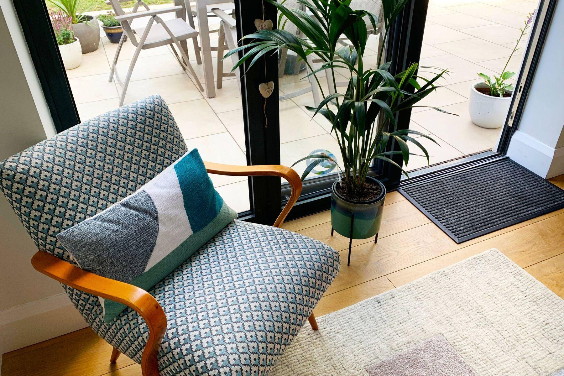 lænestol med hynde og plantepotte ved glashavedøren