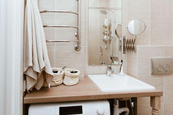 Close em pia branca de banheiro com gabinete de madeira, com objetos de tricô em cima, azulejos bege, dois espelhos e uma toalha bege