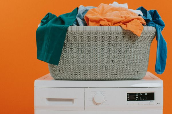 A laundry pile in a basket on top of a washing machine