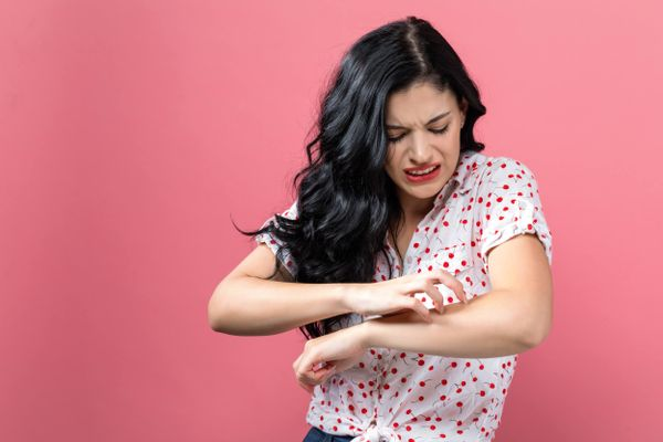 woman against pink background scratching arm for what causes eczema in adults