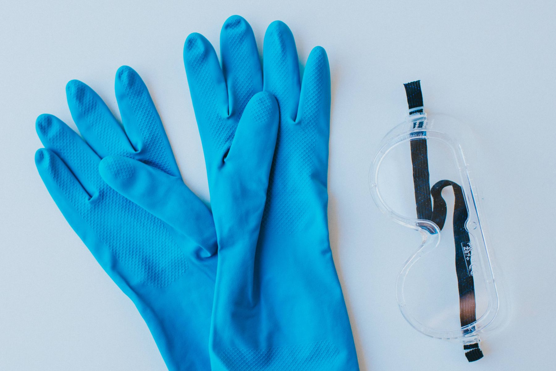 blue rubber gloves and scientific goggles for concrete cleaning