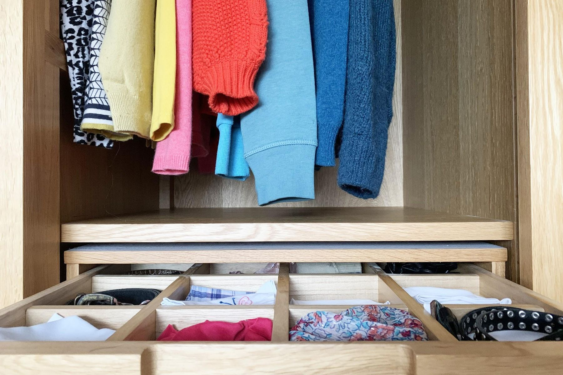 Interior de armário arrumado com roupas coloridas dobradas e penduradas