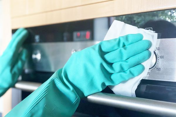 Gloved hands cleaning a stainless steel oven.