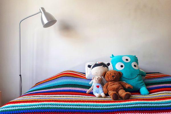 Uma boneca e três bichos de pelúcia arrumados em cima de uma cama com colcha colorida