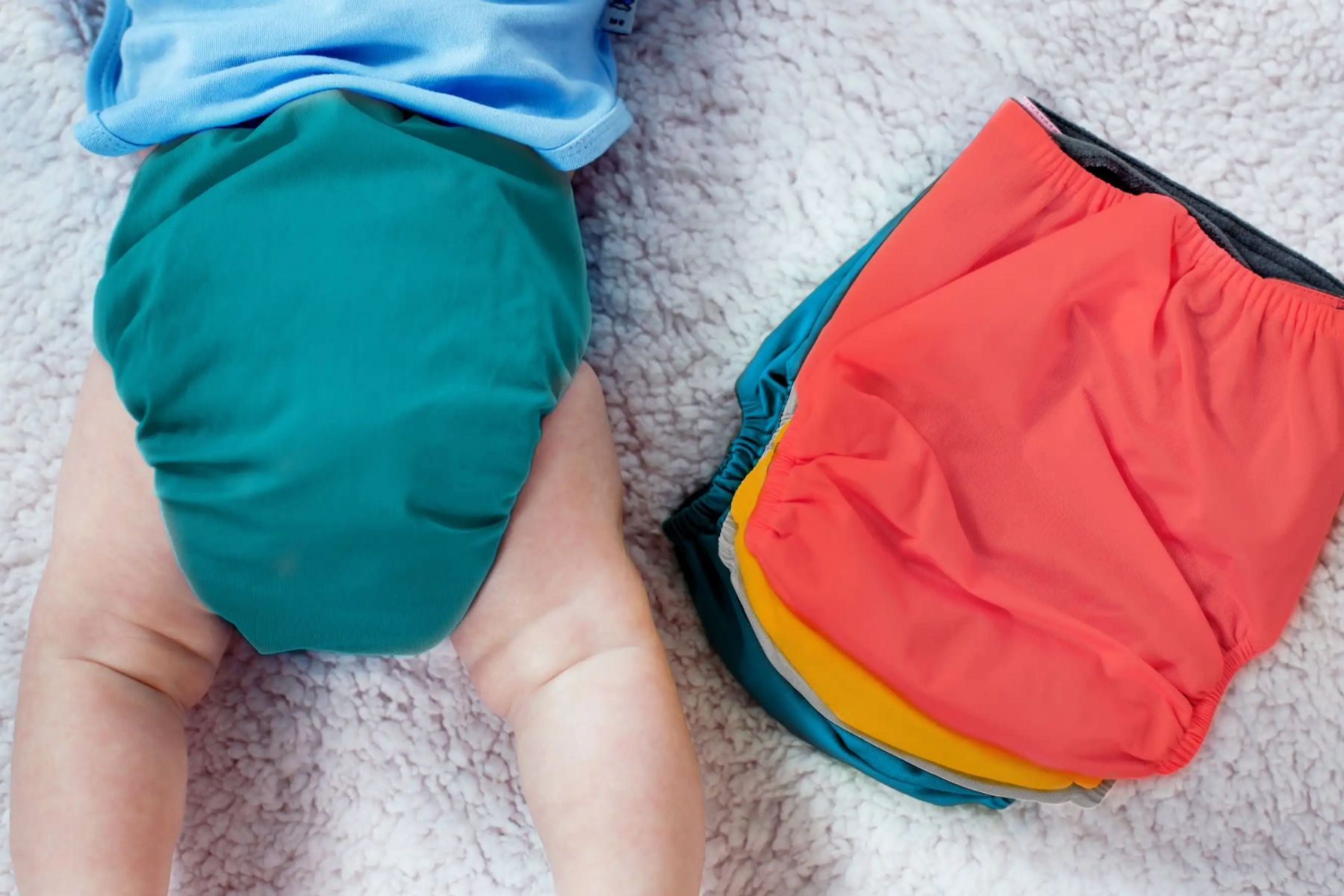 baby with a cloth nappy on next to colourful cloth nappies