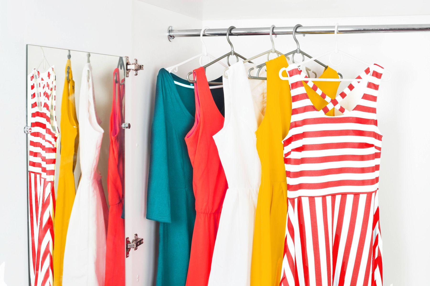 kolorowe ubrania wiszące na wieszakach w szafie