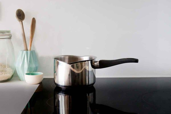 A stainless steel pot on a kitchen hob.