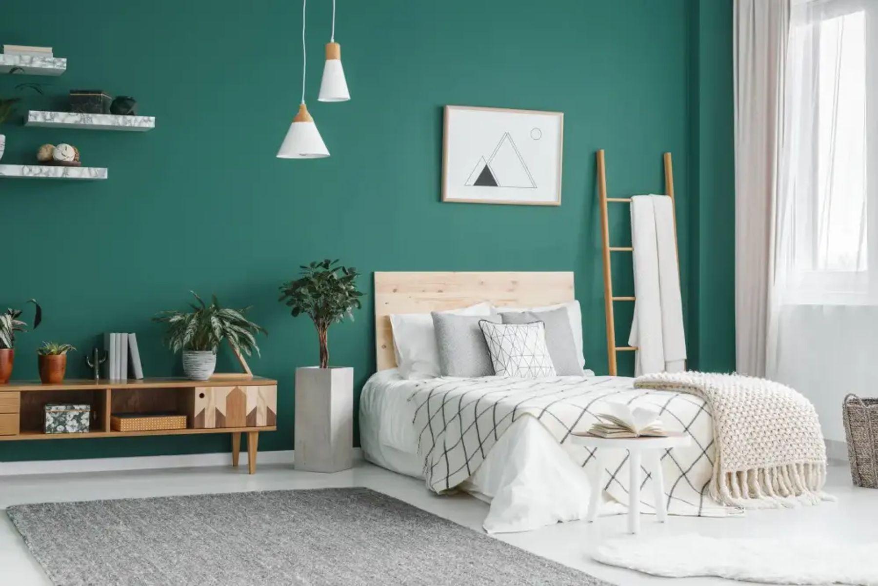 Yeşil duvarlı bir oda ve beyaz gri tonlarında nevresimli yatak