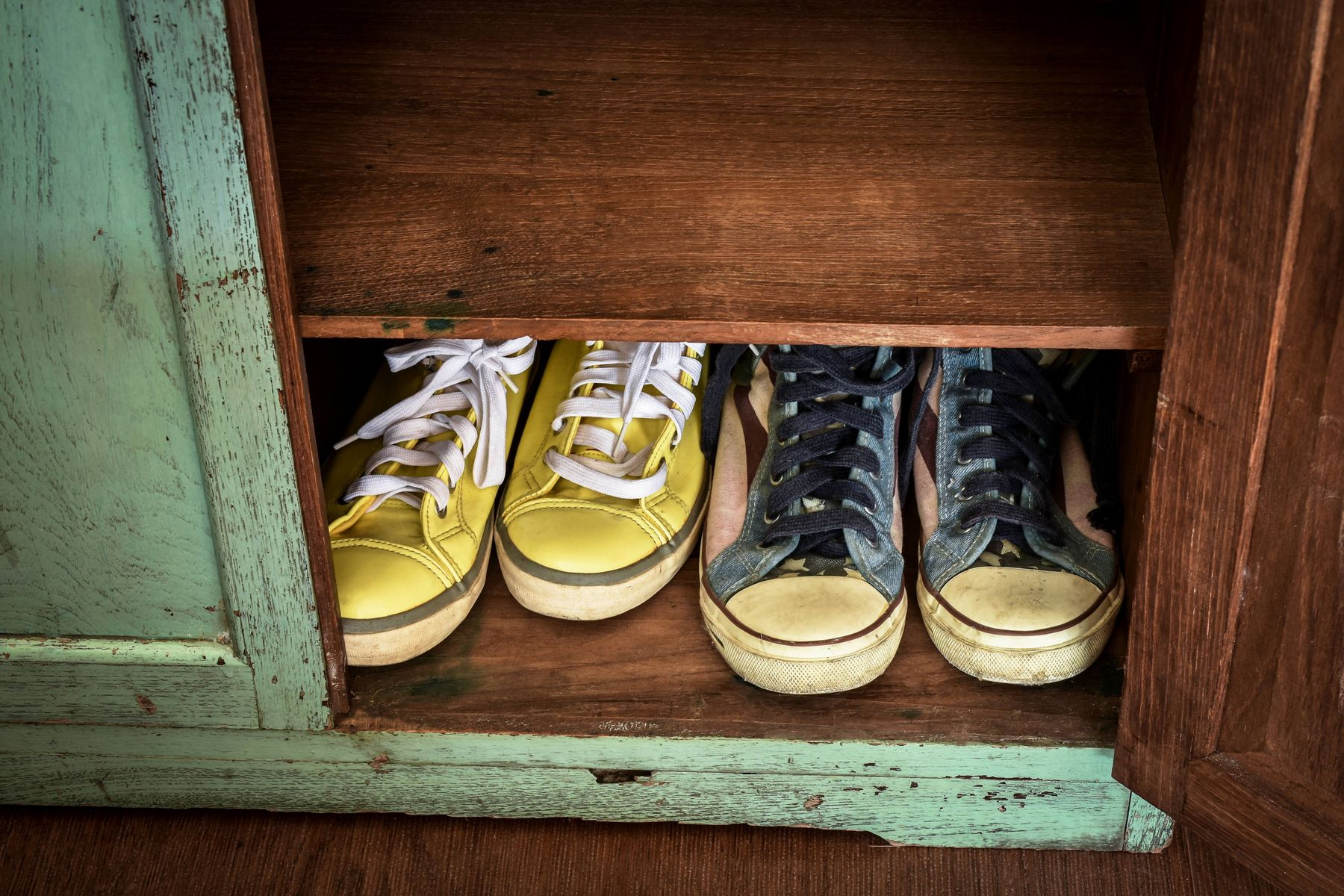 Converse shoes in distressed wood cabinet